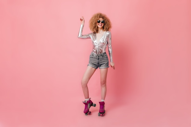 Curly blonde in brille lacht und tanzt. frau in der silbernen bluse und in den kurzen hosen wirft auf rollen im rosa studio auf.