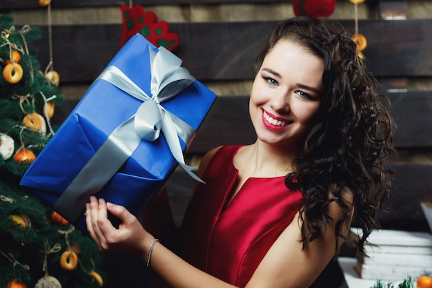 Curly brunette frau hält blaue geschenkbox