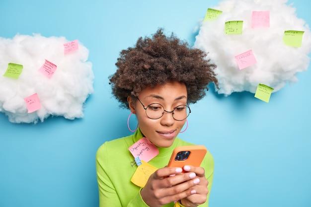 Curly haired ethnische frau konzentriert auf smartphone-display sendet textnachrichten trägt runde brille rollkragenpullover umgeben von aufklebern mit schriftlichen ideen und plänen