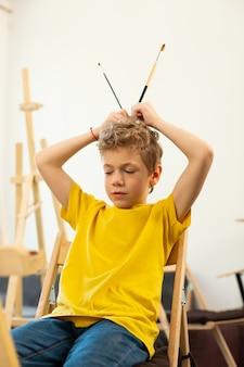 Curly junge hält zwei malpinsel, die in der kunstschule sitzen