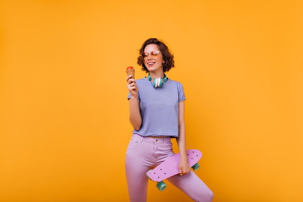 Curly mädchen in gläsern mit skateboard, das in der selbstbewussten haltung steht. innenfoto der gutaussehenden frau, die eis isst.
