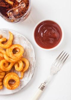 Curly pommes fast-food-snack auf holzbrett mit ketchup und glas cola auf küche. ungesundes junk food