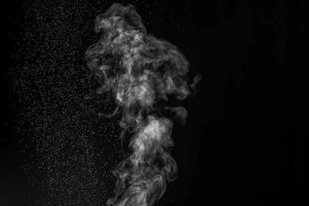 Curly weißer dampf steigt auf und spritzt wasser, das in verschiedene richtungen streut, lokalisiert auf einem schwarzen hintergrund. verdunstung von flüssigkeit und kondensation