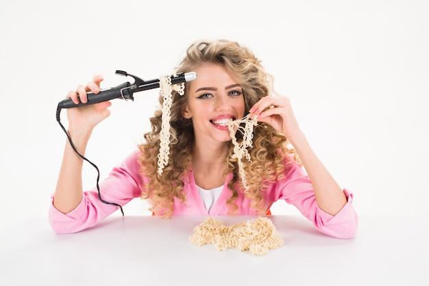 Curlyhair mädchen, das nudeln isst. fastfood-nudeln. friseur. friseur werkzeuge. schere. friseur. make-up und kosmetik.