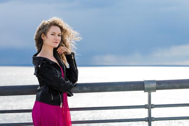 Curlyhaired kaukasische frau in einer schwarzen lederjacke und einem rosa kleid steht auf einer brücke eines düsteren himmels im wind
