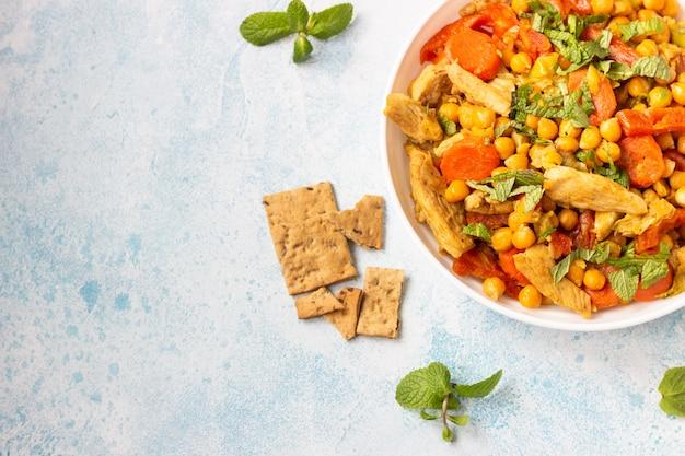 Curry mit kichererbsen, putenfleisch, karotten, lauch und getrockneten aprikosen.