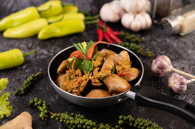 Currypulver auf einer schwarzen pfanne mit knoblauch-chili und basilikum gebraten.