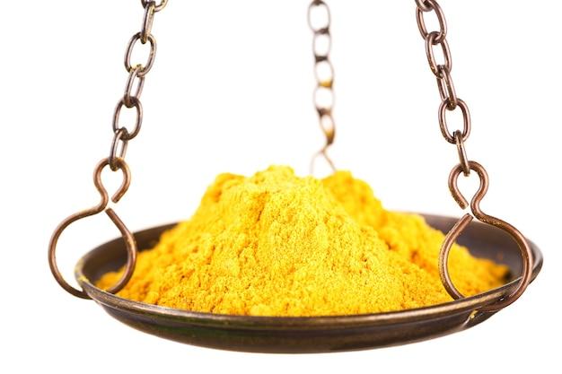 Currypulver in einer waage auf weißem hintergrund