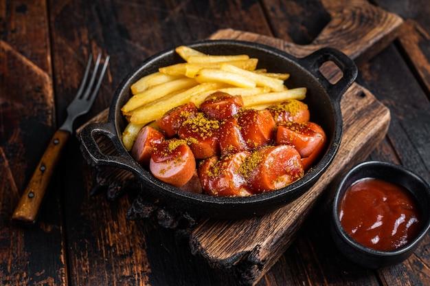 Currywurst-street-food-mahlzeit, curry-gewürz auf würsten serviert pommes frites in einer pfanne. dunkler hölzerner hintergrund. ansicht von oben.