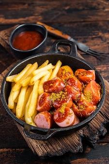 Currywurst street food mahlzeit, curry gewürz auf wurst serviert pommes in einer pfanne