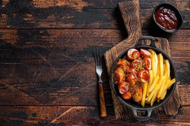 Currywurst-würstchen mit curry-gewürz auf würstchen servierten pommes frites in einer pfanne. dunkler hölzerner hintergrund. ansicht von oben. platz kopieren.