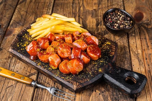 Currywurst würstchen streetfood serviert pommes frites auf einem holzbrett