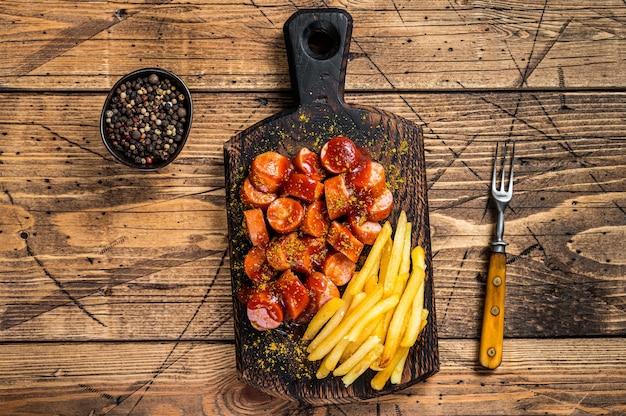 Currywurstwürste mit pommes frites auf einem holzbrett. holztisch. draufsicht.
