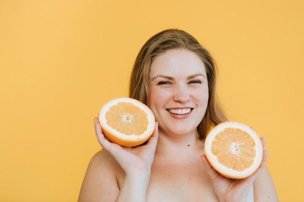 Curvy blonde frau, die zwei frische orangen hält