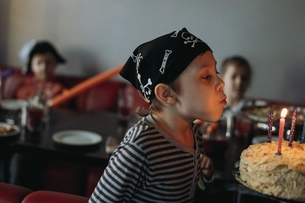 Cuta kaukasischer junge in piratenbandana und gestolpertem t-shirt, das kerzen auf geburtstagskuchen bläst. foto in hoher qualität