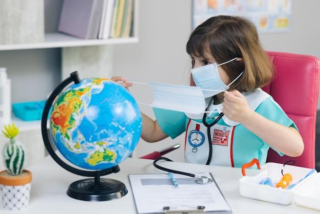 Cute kid mädchen arzt legt eine maske auf den globus des planeten erde kleines mädchen in einem arztanzug gekleidet behandelt den planeten erde.