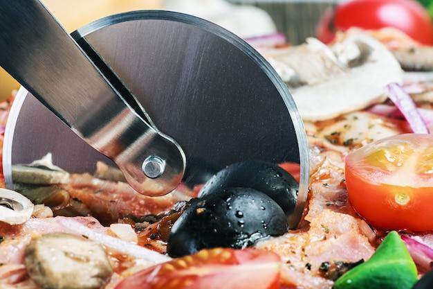 Cutter schneidet eine frische pizza mit pilzen
