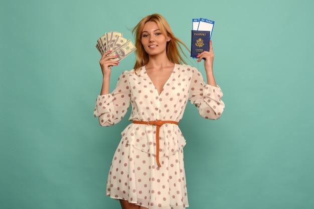Cuty young woman hält tickets mit pass und doller geld auf blue studio hintergrund