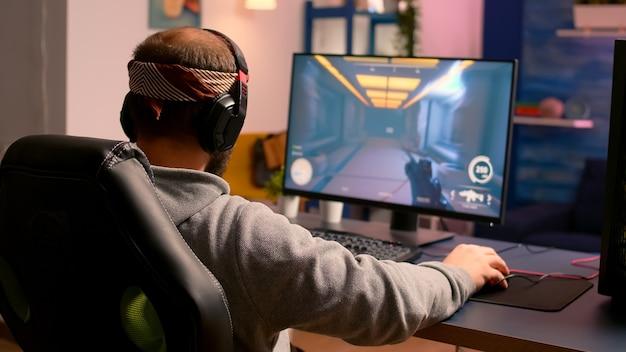 Cyber-gamer, der hände und nacken streckt, bevor er online-videospiele mit rgb-tastatur und -maus spielt. spieler, die während des gaming-turniers online-spiele durchführen