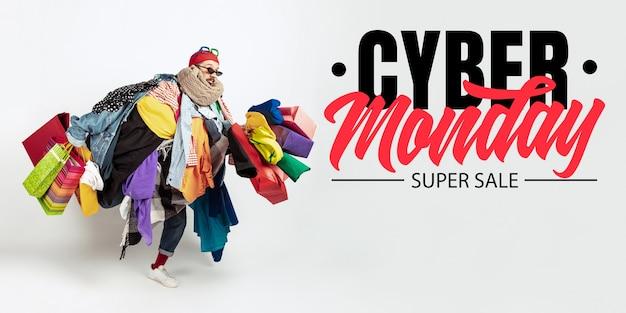 Cyber-montag, finanzkonzept. mann süchtig nach verkauf und kleidung. weibliches modell, das zu viel bunte kleidung trägt. mode, stil, schwarzer freitag, verkauf, einkäufe, geld, online-kauf. flyer für anzeige.