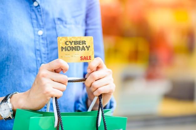 Cyber-montag-verkaufskonzept. frau, die einkaufstaschen und kreditkarte hält
