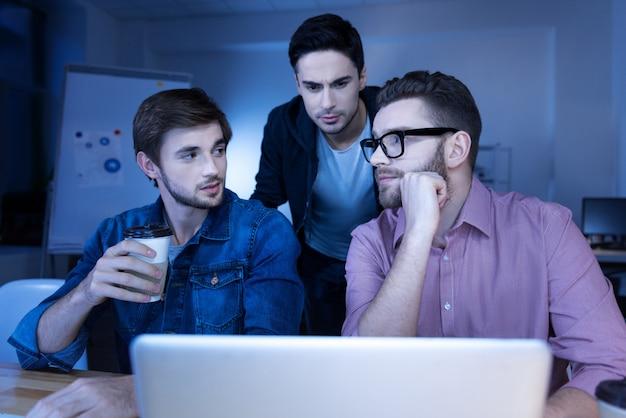 Cyberkriminalität begehen. kluge, gutaussehende männliche hacker, die zusammenarbeiten und sich gegenseitig ansehen, während sie sich in eine website hacken