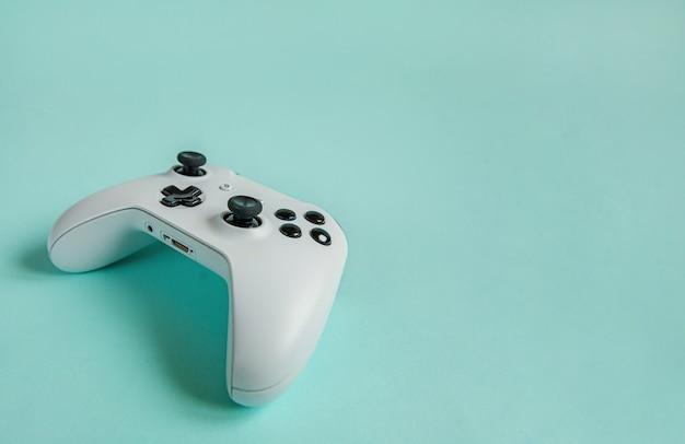 Cyberspace-symbol. weißes joystick-gamepad, spielekonsole lokalisiert auf pastellblauem buntem trendigem hintergrund. konfrontationskonzept zur kontrolle von videospielen für computerspiele.
