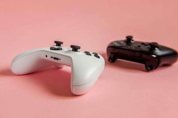Cyberspace-symbol. weißes und schwarzes zwei-joystick-gamepad, spielekonsole auf pastellrosa bunter trendiger pin-up-oberfläche. konfrontationskonzept zur kontrolle von videospielen für computerspiele.