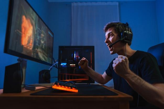 Cybersport junger profi-spieler, der mit dem gewinn des spiels zufrieden ist, sich aufgeregt fühlt und ja-handbewegung zeigt
