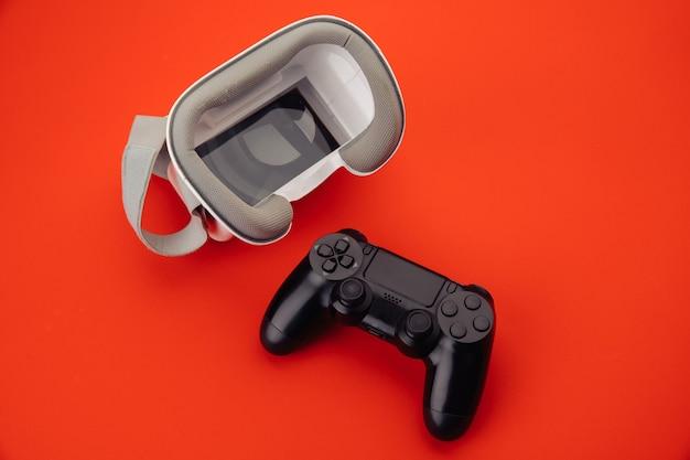 Cybersport-konzept vr virtual-reality-brille mit rückseitigem gamepad auf rotem hintergrund