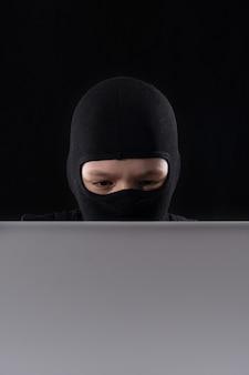 Cyberterrorist in einer maske in einer maske auf einem schwarzen raum hinter einem laptop.