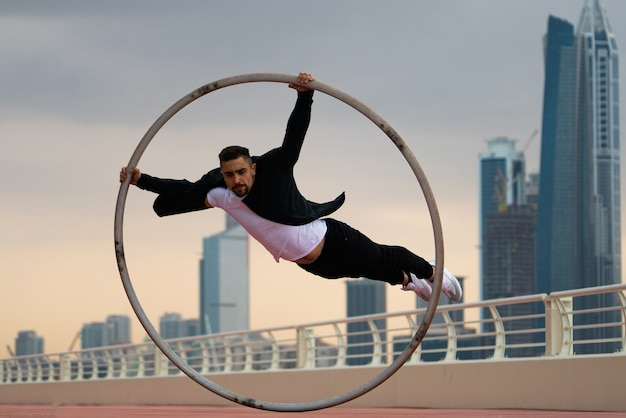 Cyr wheel-künstler, der während des sonnenuntergangs schwarze und weiße elegante kleidung mit stadtbildhintergrund von dubai trägt.