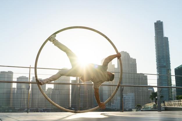 Cyr wheel-künstler mit stadtbildhintergrund von dubai während des sonnenuntergangs.