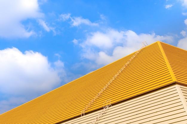 Dach auf einem gelben hintergrund des blauen himmels.