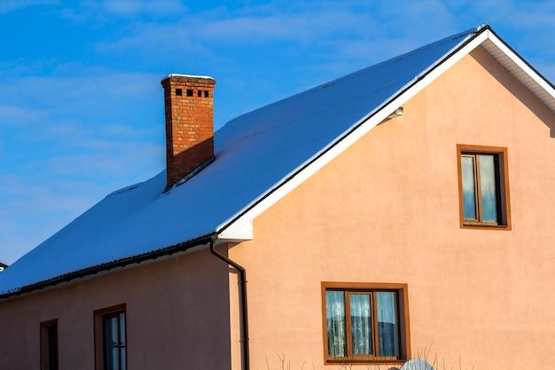 Dach eines neugebauten hauses mit schönem fenster und kamin.