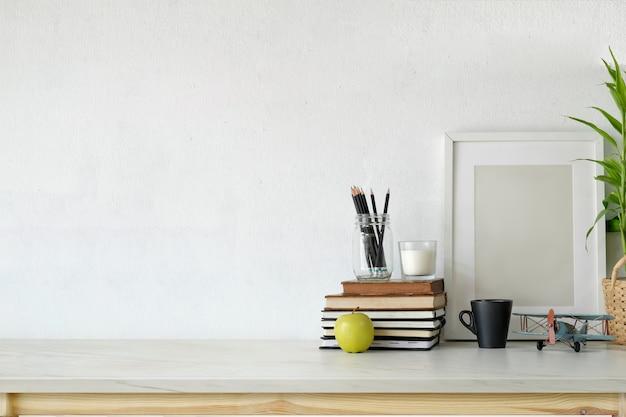 Dachbodenarbeitsplatz mit leerem plakat auf weißem hölzernem schreibtisch.
