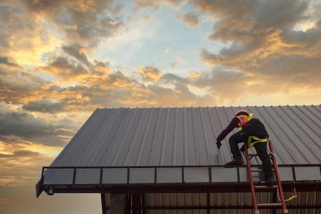 Dachdecker bauarbeiter installieren neues dach, dachwerkzeuge, elektrische bohrmaschine auf neuen dächern mit blech.