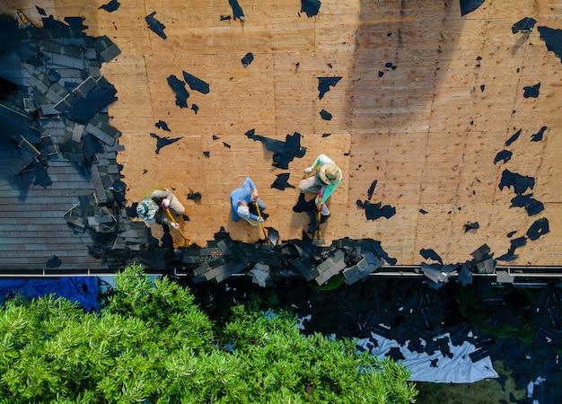 Dachdecker ersetzen schindeln, die beschädigt wurden und das wohngebäude ersetzen müssen