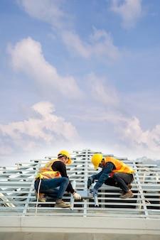 Dachdecker in einheitlicher schutzkleidung und handschuhen, luft- oder druckluftnagelpistole verwenden und betondachziegel auf dem neuen dach verlegen, konzept des im bau befindlichen wohngebäudes.
