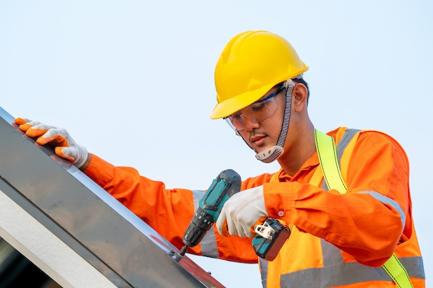 Dachdecker in speziellem schutz, der ein neues dach auf dem dach installiert.