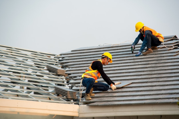 Dachdecker in speziellen arbeitsschutzkleidung und handschuhen, luftpistole verwenden und betondachziegel auf dem neuen dach verlegen, konzept des im bau befindlichen wohngebäudes.