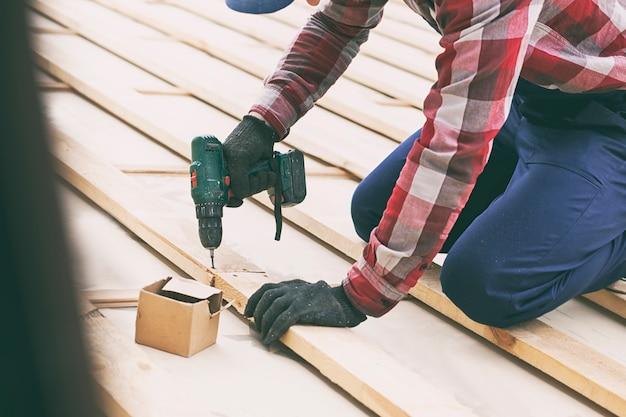 Dachdecker schraubt eine planke auf das dach