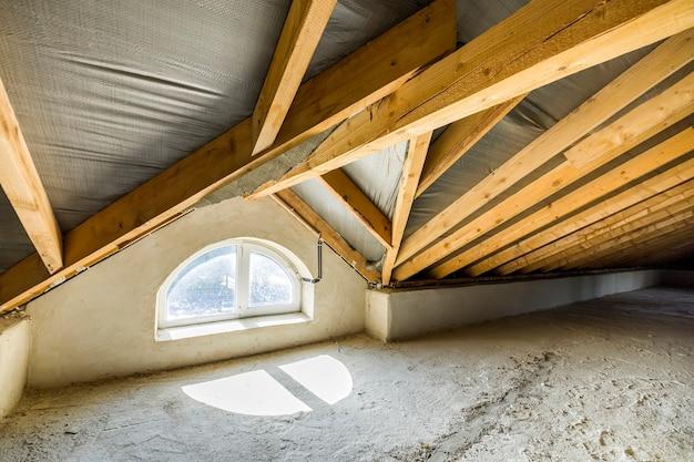 Dachgeschoss eines gebäudes mit holzbalken einer dachkonstruktion und einem kleinen fenster.