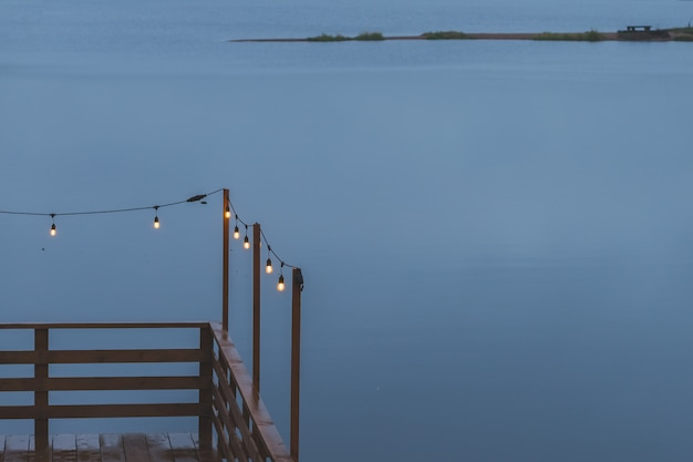 Dämmerung, grauer farbhimmel am seeufer, elektrische lampen als girlande und holzterrasse, pier. romantische atmosphäre des abends. kaffeeterrasse. retro girlande für wohnkultur.