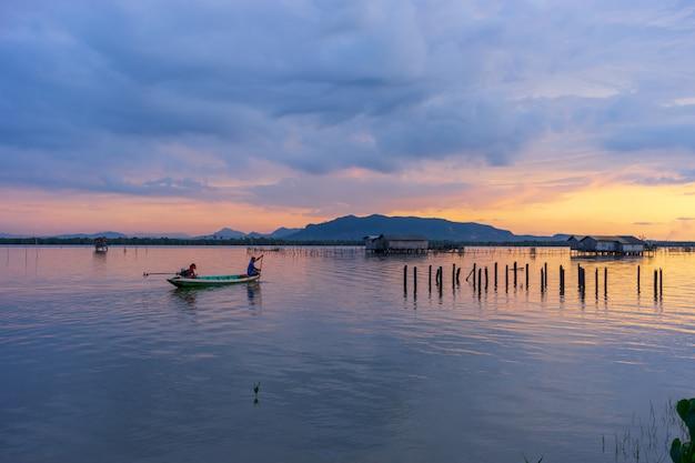 Dämmerungshimmel während des sonnenuntergangs im see mit ansicht des berges, des bewölkten himmels und des kleinen fischers