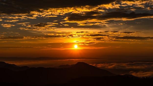 Dämmerungslandschaft der sonnenuntergang- und wolkenhimmel mit orangen- und schattenbildgebirgsvordergrund