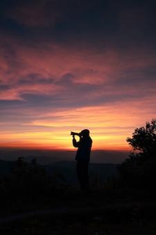 Dämmerungslicht mit einem fotografen, der ein foto nach dem sonnenuntergang macht