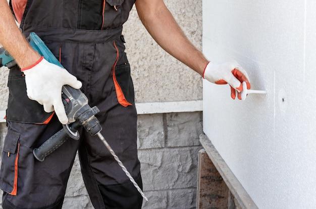 Dämmung des hauses mit polyschaum. der arbeiter repariert eine styroporplatte mit kunststoffdübeln.