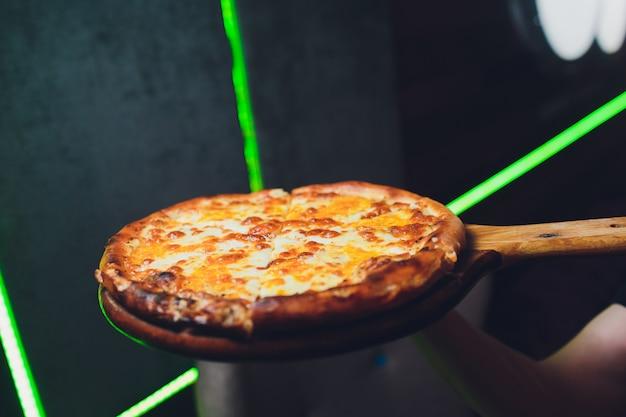 Dämpfende heiße leckere italienische margarita-pizza frisch aus dem pizzaofen in einer pizzeria, serviert auf einem langstieligen holzbrett mit copyspace dahinter.