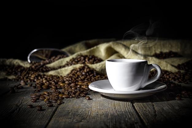 Dämpfende tasse kaffee auf hölzernem hintergrund